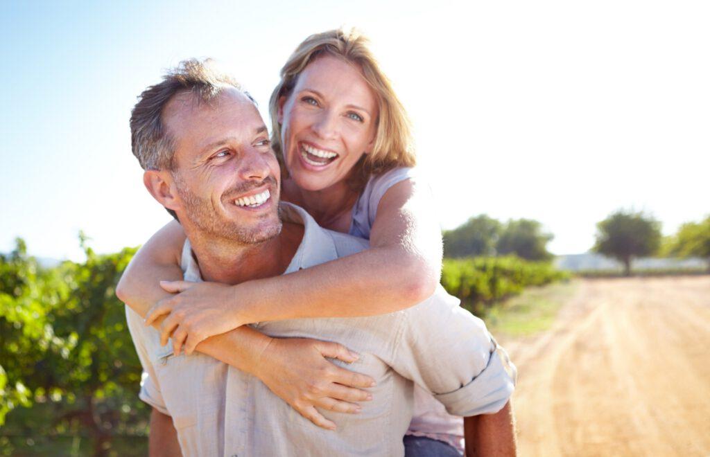 Ein Mann trägt eine lachende Frau auf dem Rücken.