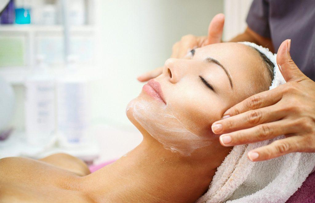 Frau erhält ein Gesichtspeeling mit Massage.