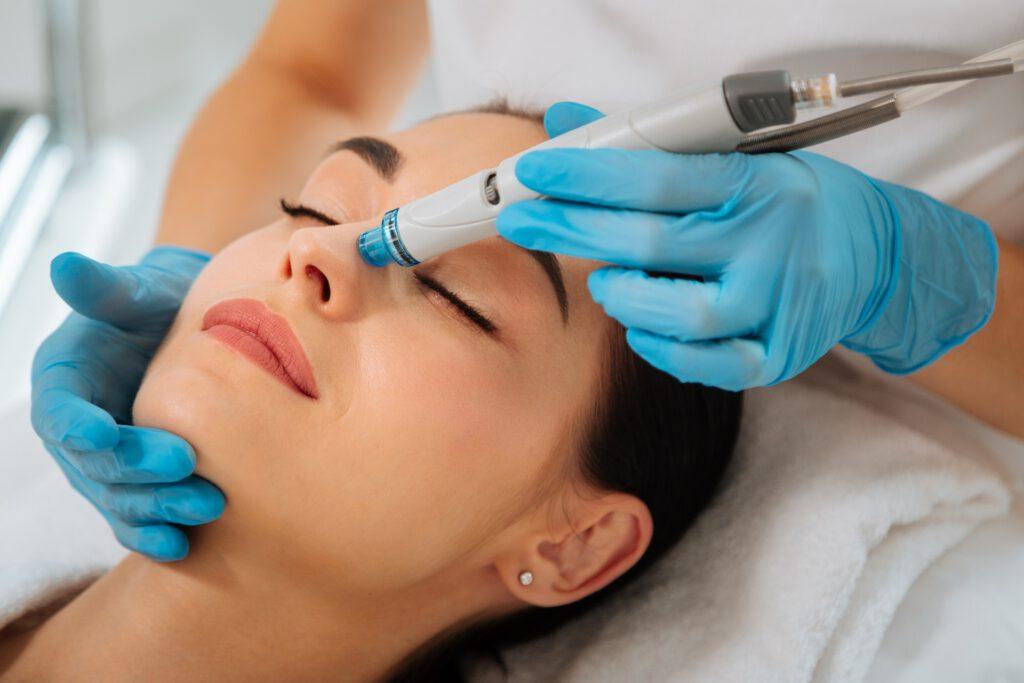 Frau erhält medizinkosmetische Gesichtsbehandlung mit HydraFacial und hat entspannt die Augen geschlossen.