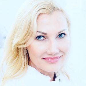 Blonde Frau in weißem Kittel lächelt in Kamera