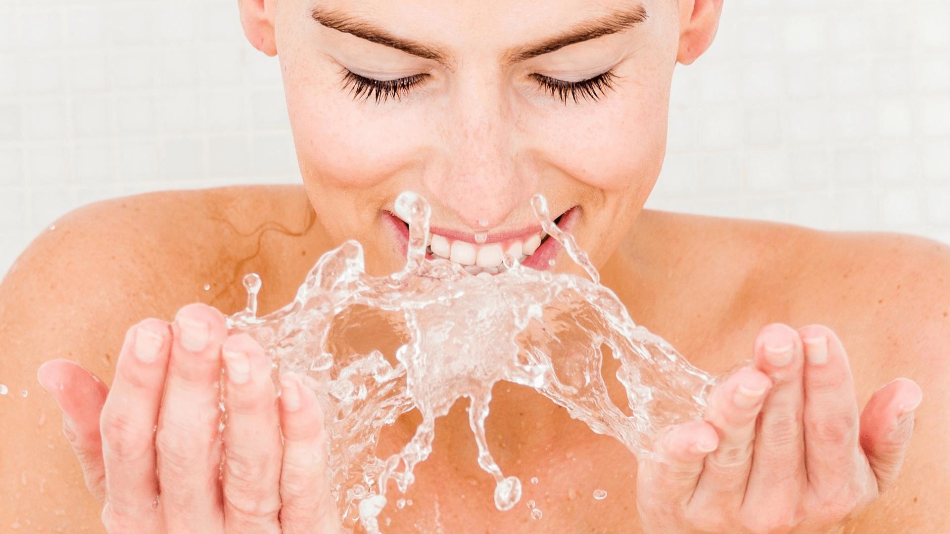 Junge Frau wäscht sich Gesicht mit Wasser.